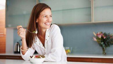 smiling happy woman eating food in kitchen 390x220 - چگونه کمتر غذا بخوریم؟ 15 راه مهار گرسنگی و کاهش اشتها