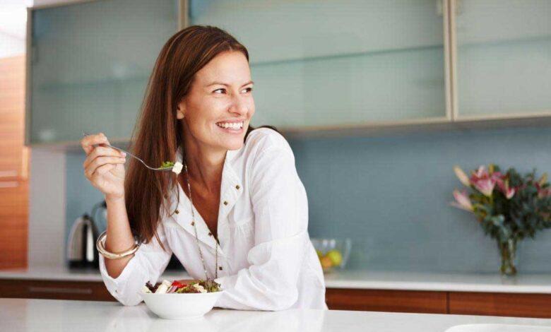smiling happy woman eating food in kitchen 780x470 - چگونه کمتر غذا بخوریم؟ 15 راه مهار گرسنگی و کاهش اشتها
